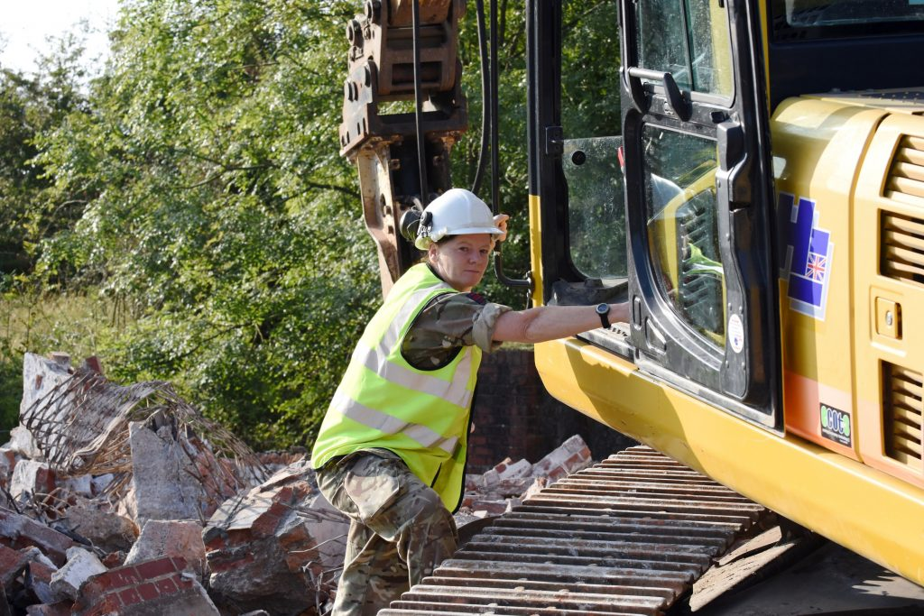 Army Reserve Royal Engineer plant operator climbing into plant during weekend training