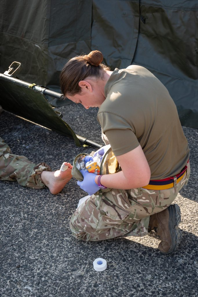 An Army Reservist medic of The Royal Monmouthshire Royal Engineers (Militia) tends to the sore feet of one of the other soldiers during Ex MILITIA THUNDER 18, the 2018 Annual Camp for this Royal Engineer unit.