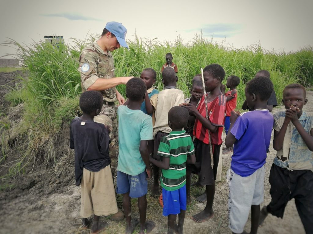 A Royal Monmouthshire Royal Engineers (Militia) soldier, deployed on operations to South Sudan as part of UNMISS, entertains displaced children by the Tri-Star facility.